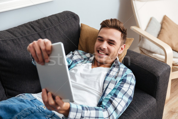 Bristle man lies on sofa and playing at tablet computer Stock photo © deandrobot