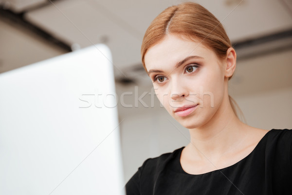 Concentrated lady worker sitting in office while using laptop Stock photo © deandrobot