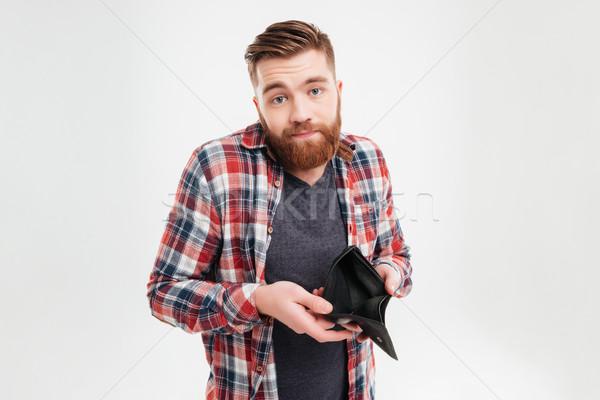 Zaklatott fiatalember tart üres pénztárca fiatal Stock fotó © deandrobot