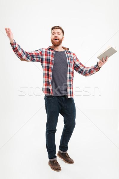 Fiatal szakállas férfi tart könyv gesztikulál Stock fotó © deandrobot