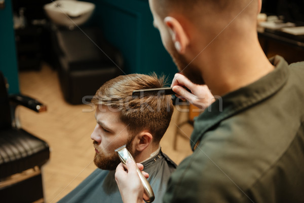 Handsome man getting haircut by hairdresser with razor Stock photo © deandrobot