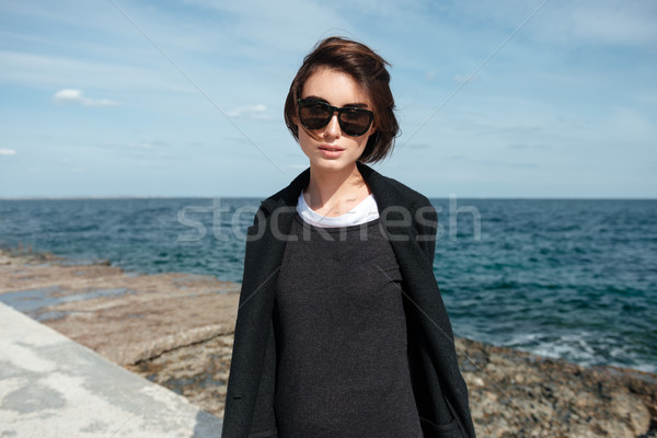 Pretty woman in sunglasses and black jacket on the seaside Stock photo © deandrobot
