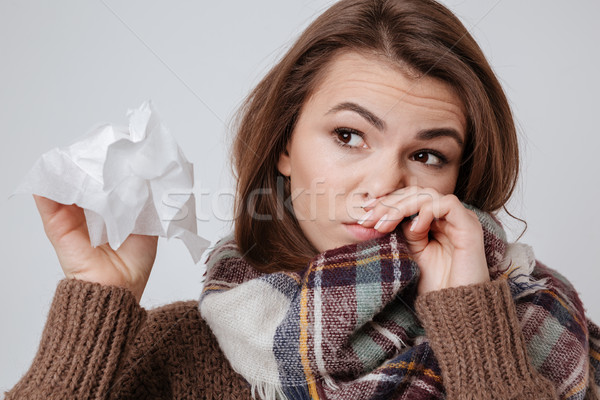 Sick young lady with napkin over gray background. Stock photo © deandrobot