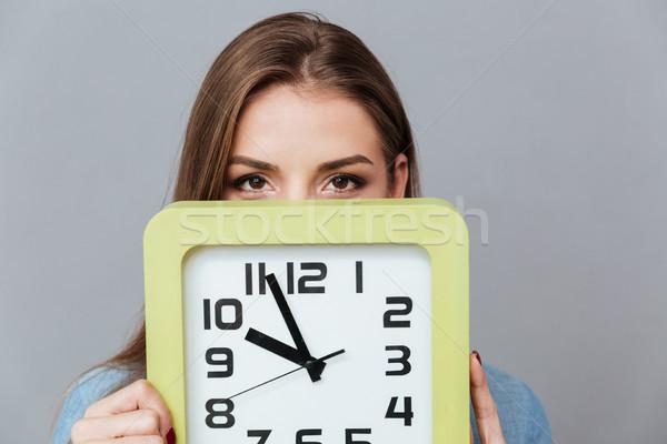 Mujer camisa ocultación detrás reloj estudio Foto stock © deandrobot