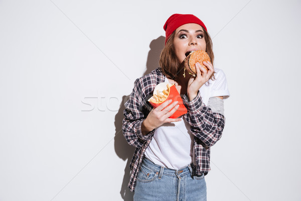 Hungry young woman eating fries and burger Stock photo © deandrobot