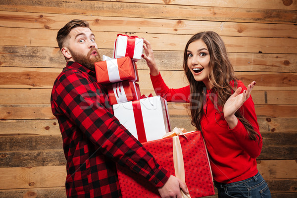 Cheerful happy couple standing with heap of xmas present boxes Stock photo © deandrobot