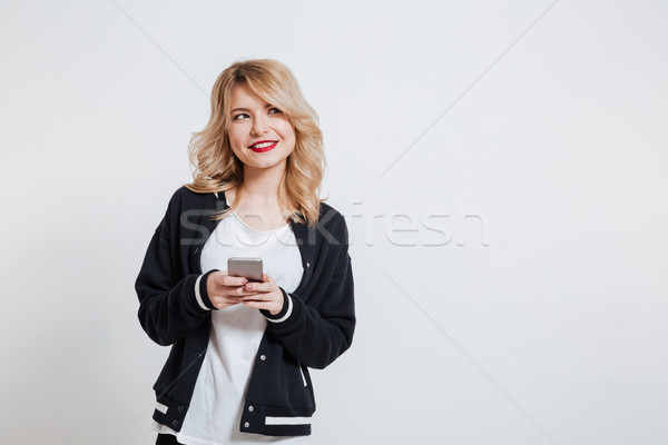 Girl in casual clothes holding mobile phone and looking away Stock photo © deandrobot