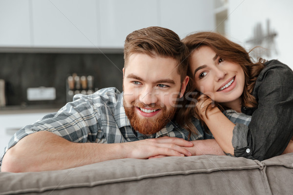 Pretty loving couple sitting on sofa indoors and looking aside. Stock photo © deandrobot