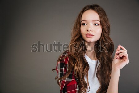 Thoughtful beautiful young woman in plaid shirt standing and thinking Stock photo © deandrobot