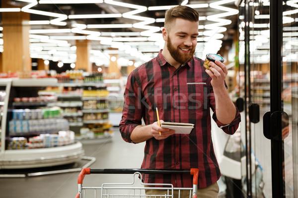 Glimlachend jonge man permanente supermarkt kiezen producten Stockfoto © deandrobot