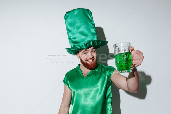Happy bearded man in green costume holding cup Stock photo © deandrobot