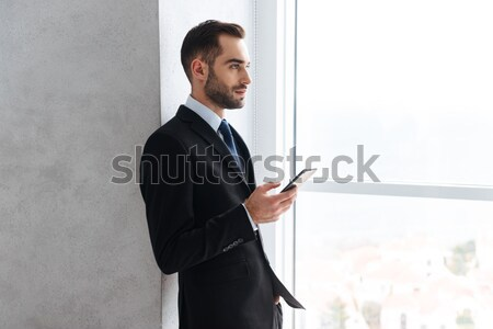Happy young businessman showing thumbs up gesture. Stock photo © deandrobot