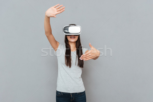 Pleased woman using virtual reality device Stock photo © deandrobot
