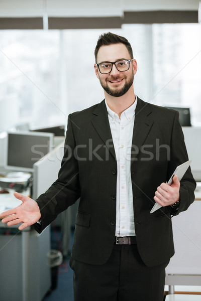 Vertical image of Bearded business man holding tablet computer Stock photo © deandrobot