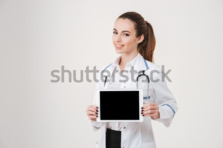 Confident young female nurse or doctor in white coat Stock photo © deandrobot
