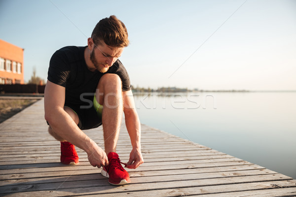 Stock photo: Portrait of a man tying shoelaces on sports shoe