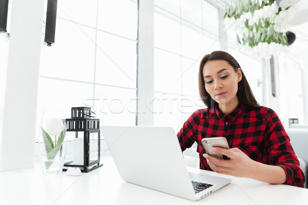 Hardworking woman using smartphone while working with laptop Stock photo © deandrobot