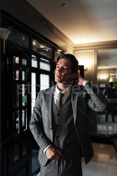 Jóképű középkorú üzletember öltöny áll lobbi Stock fotó © deandrobot