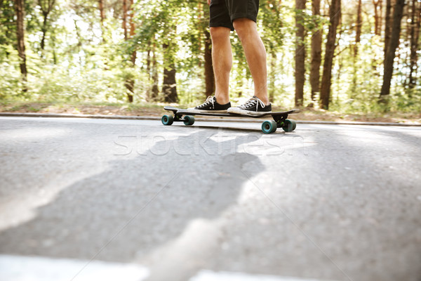 Picture of young man on skateboard outdoors. Stock photo © deandrobot