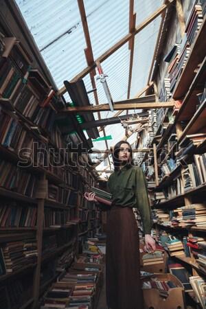 Mulher jovem casaco em pé livro armazém moda Foto stock © deandrobot