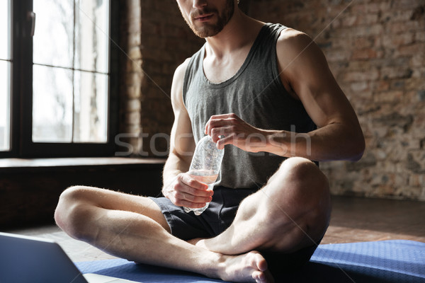 Cropped image of strong sportsman drinking water Stock photo © deandrobot