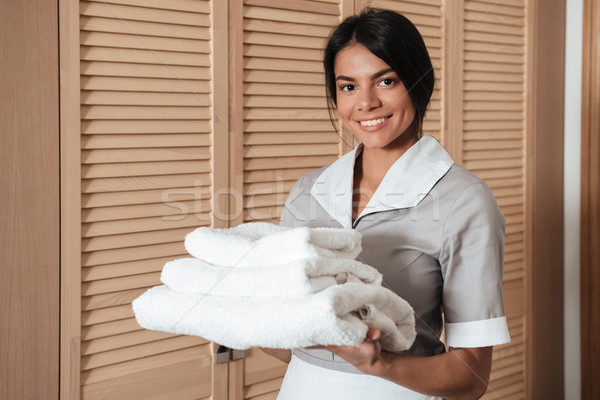 Portrait of a hotel maid holding fresh clean folded towels Stock photo © deandrobot