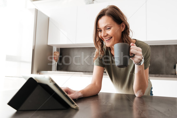 Happy Casual woman drinking coffee and using tablet computer Stock photo © deandrobot