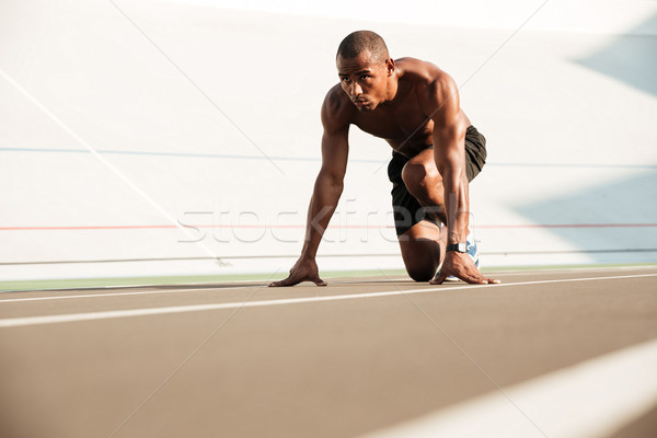 Young african runner starting and preparing to run Stock photo © deandrobot