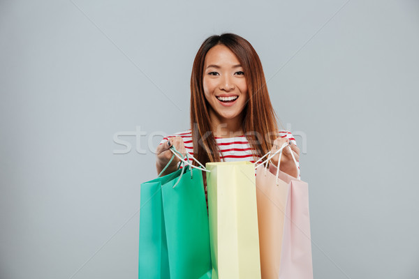 Happy asian woman in sweater holding packages Stock photo © deandrobot
