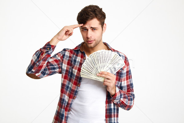 Portrait of a casual man holding bunch of money banknotes Stock photo © deandrobot