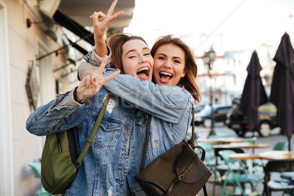 Stock photo: Photo of two charming brunette female friends hugging each other