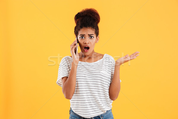 Shocked lady talking on smartphone and looking camera isolated Stock photo © deandrobot