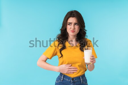 Thoghtful woman holding international passport isolated over yellow Stock photo © deandrobot