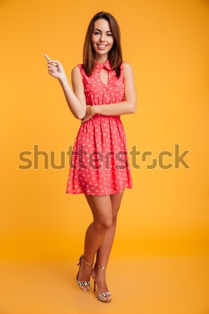 Full-length portrait of young happy woman in red dress showing p Stock photo © deandrobot