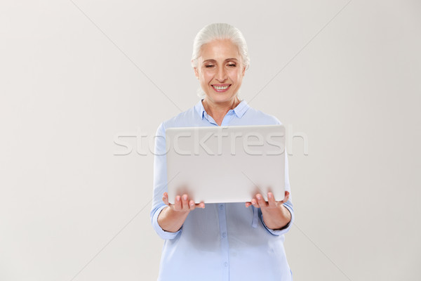 Mature woman holding and using laptop computer isolated Stock photo © deandrobot