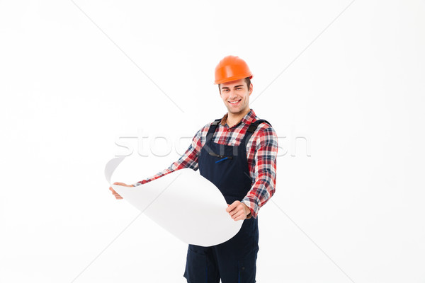 Portrait of a happy young male builder holding paper draft Stock photo © deandrobot