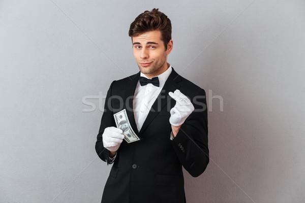 Jóképű fiatal pincér tart pénz fotó Stock fotó © deandrobot