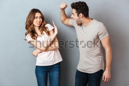Knap jonge man tonen biceps verwonderd vriendin Stockfoto © deandrobot