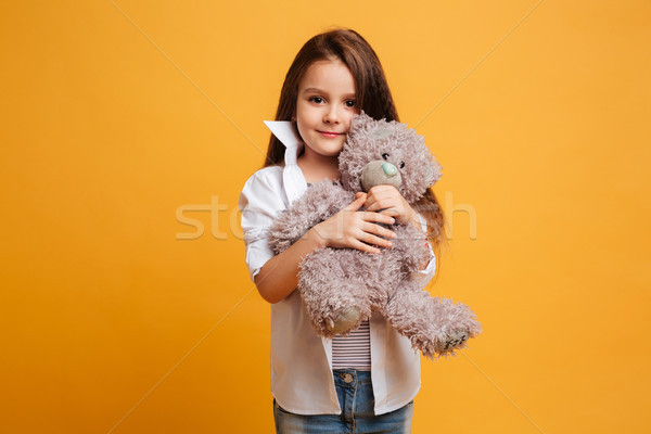 Cute little girl child holding toy teddy bear in hands Stock photo © deandrobot