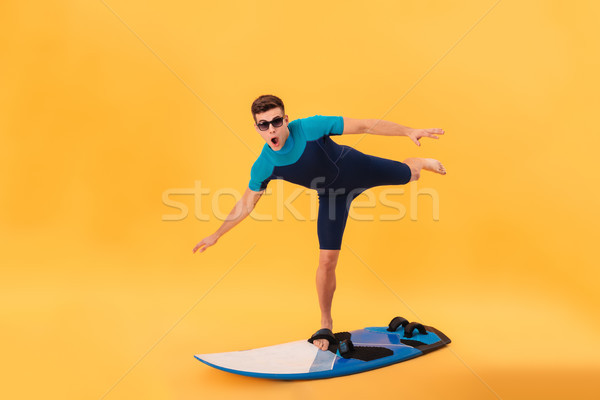 Picture of Funny surfer in wetsuit and sunglasses using surfboard Stock photo © deandrobot
