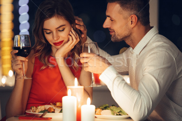 Handsome man iron his girlfriend while have romantic dinner in the evening Stock photo © deandrobot