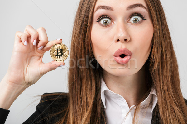Surprised young woman holding golden bitcoin and looking camera with opened mouth Stock photo © deandrobot