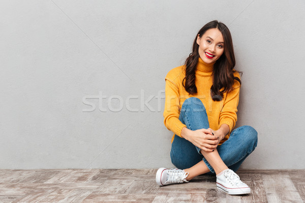 Pleased brunette woman in sweater sitting on the floor Stock photo © deandrobot
