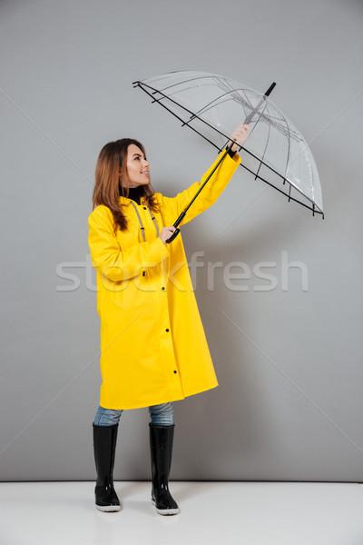 Full length portrait of a smiling girl dressed in raincoat Stock photo © deandrobot