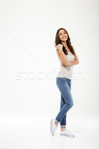 Full length image of Pleased brunette woman posing sideways Stock photo © deandrobot