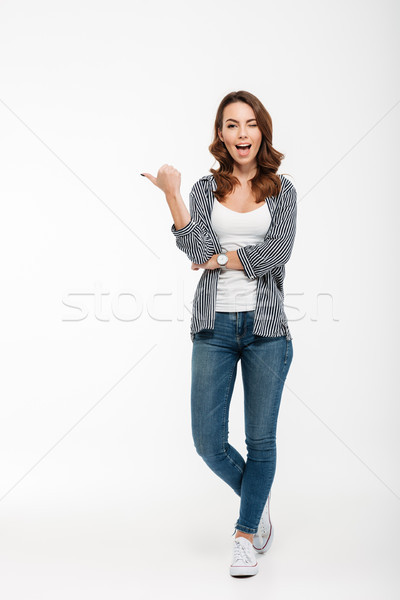 Full length portrait of a happy casual girl winking Stock photo © deandrobot