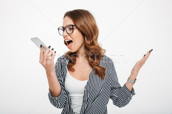 Portrait of an angry casual girl yelling at mobile phone Stock photo © deandrobot