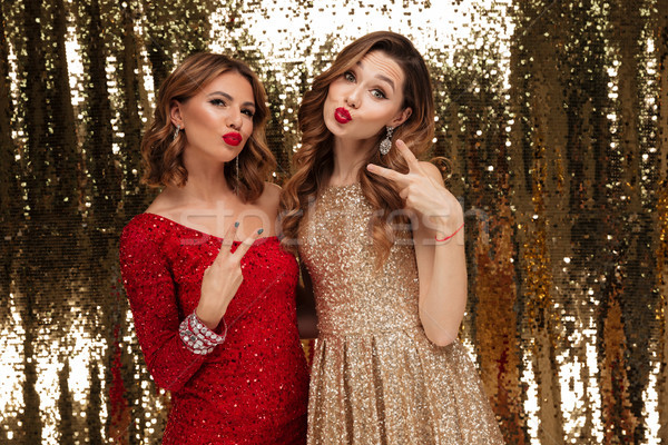 Portrait of two joyful happy women in sparkly dresses Stock photo © deandrobot