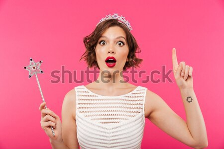 Amazing young woman have an idea pointing. Stock photo © deandrobot