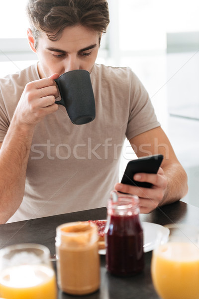 Portrait of young focused man drinking tea and using smartphone Stock photo © deandrobot
